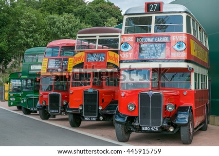 WEYBRIDGE, SURREY, UK - AUGUST 18: A line of vintage red and green vintage buses outside the transport museum at Brooklands Motor Museum, Weybridge in 2013. - stock photo