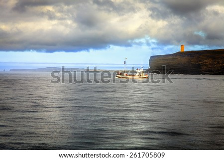Whale watching ship leaving Husavik Harbor in Northern Iceland - stock photo