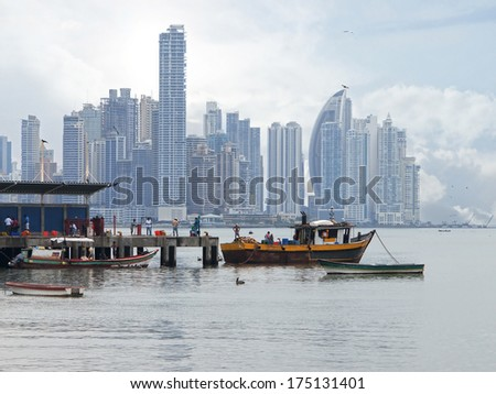 Wharf with fishing boats in foreground and skyscrapers in background, Panama City , Panama, Central America