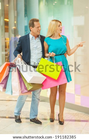What a beautiful dress! Full length of mature couple shopping together while woman pointing mannequin