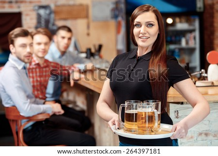 What a beautiful girl. Selective focus on beautiful waitress holding a tray with beer glasses while young men are looking at her with amazement - stock photo