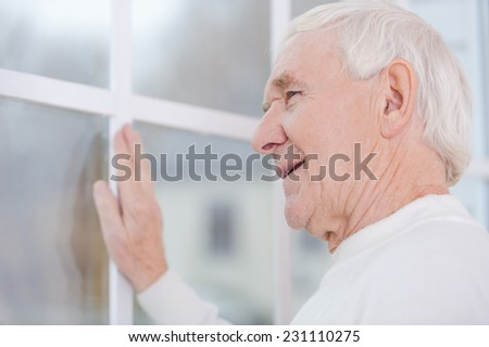 What a beautiful view!  Cheerful senior man keeping hand on window frame and looking through the window  - stock photo