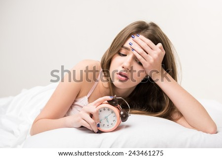 What a long night. Young beautiful woman lying in bed and looking at clock failing to fall asleep - stock photo