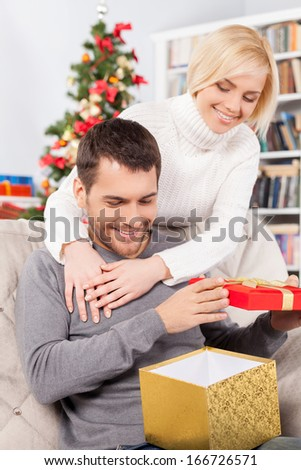 What a nice present! Handsome young man sitting on the couch and holding a gift box while her girlfriend standing behind him and smiling - stock photo