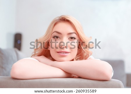 What a pleasure to do nothing. Attractive young smiling woman lying on the couch and looking at camera - stock photo