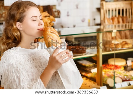What a smell. Closeup shot of a young attractive woman smelling fresh warm bread with pleasure and smiling in a local bakery - stock photo