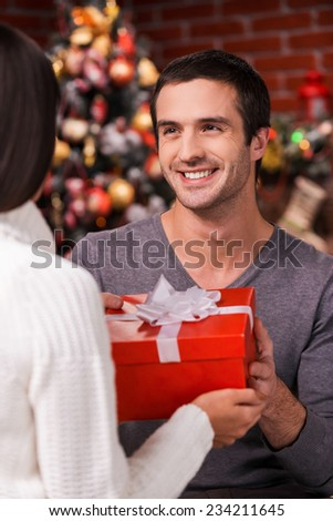 What a surprise! Rear view of young man giving a red gift box to his girlfriend with Christmas Tree in the background  - stock photo