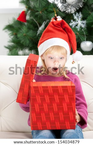 What a surprise! Surprised little girl opening Christmas gift box - stock photo