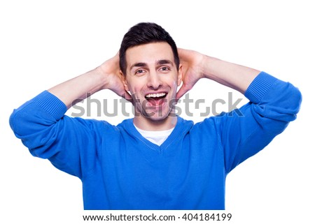 What a surprise! Surprised young man in casual wear holding hands behind head and smiling while standing isolated on white background - stock photo