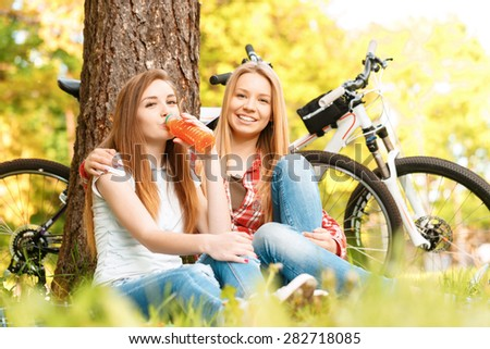 What a wonderful picnic. Two young beautiful girls with long hair sitting on a blue checkered mat under a tree smiling and drinking fruit juice, their bikes standing near in a green park - stock photo