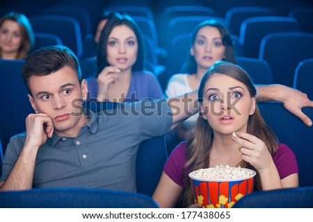 What am I doing here? Bored young man sitting close to his excited woman while watching movie at the cinema - stock photo