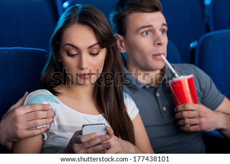 What an exciting movie! Excited young couple eating popcorn and drinking soda while watching movie at the cinema  - stock photo