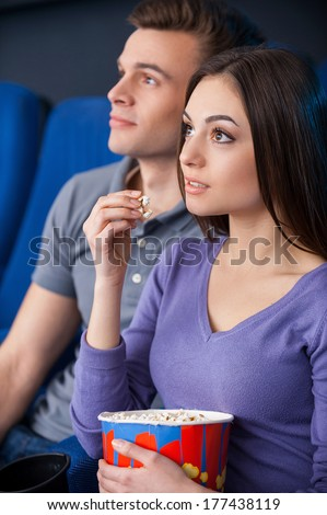 What an exciting movie! Excited young couple eating popcorn while watching movie at the cinema  - stock photo