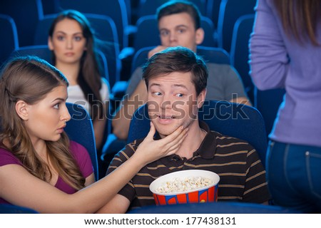 What are you looking at? Young man looking at the woman buttocks while sitting together with his girlfriend at the cinema  - stock photo