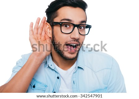 What did you say? Curious young Indian man holing hand near ear and looking at camera while standing against white background - stock photo