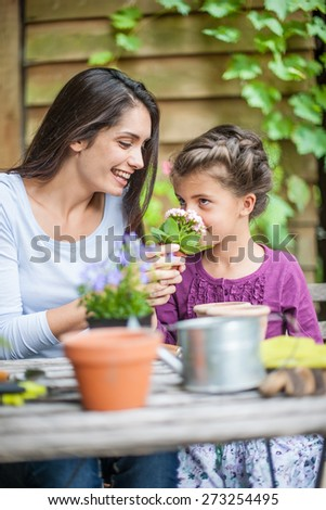 What do you smell? Mother and daughter are doing gardening - stock photo
