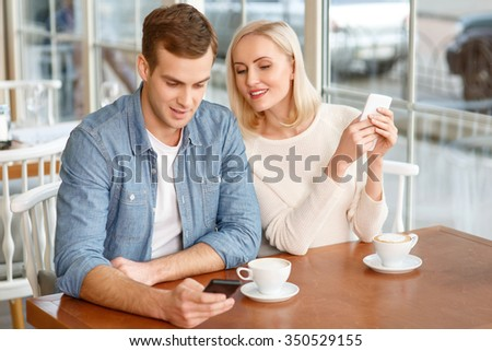 What is here. Delighted smiling young couple sitting in the cafe and holding mobile phones while resting together - stock photo