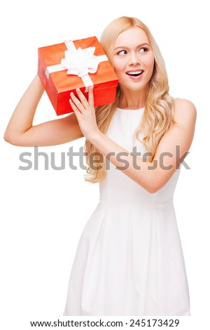 What is inside? Curious young blond hair woman holding gift box and trying to guess what is inside while standing isolated on white background - stock photo