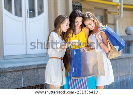 What is new in shopping. Three girlfriends are standing and looking is a shopping bag, while going shopping during weekend - stock photo
