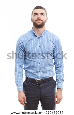 What is there. Portrait of young handsome man with beard standing against isolated white background and looking up.