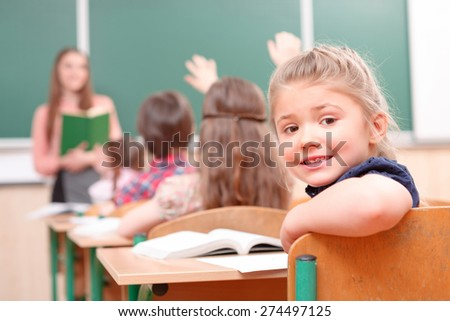 What is there. Pupil with raised hand turned away from teacher in classroom. - stock photo