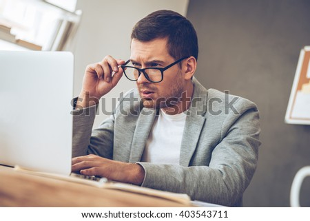 What is this? Handsome young man looking at his laptop and adjusting his glasses while sitting at his working place - stock photo