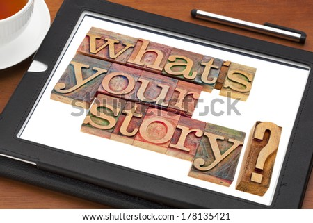 what is your story question in vintage wooden letterpress printing blocks on a digital tablet with a cup of tea - stock photo