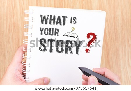 What is your story work on white ring binder notebook with hand holding pencil on wood table,Business concept - stock photo