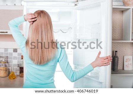 What's for dinner? Pretty blonde standing near open empty fridge. Back view photo of thoughtful young woman. She looking at fridge