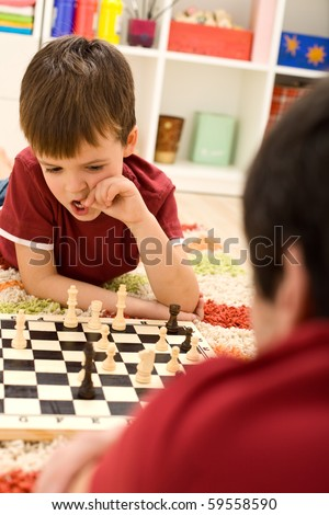 What should I do now - kid playing chess thinking hard biting his thumbnails - stock photo