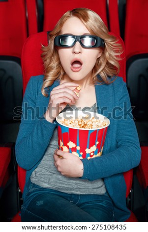 What story line. Amazed blond woman in 3 d glasses eating popcorn in cinema while watching film