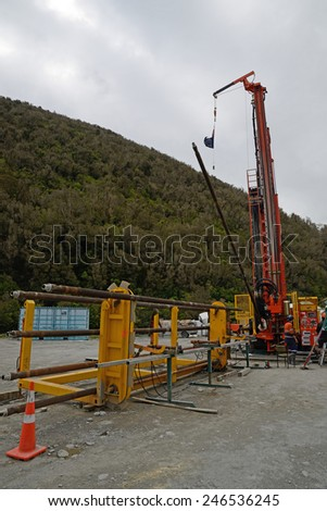 WHATAROA, NEW ZEALAND, DECEMBER 5, 2014: Drillers load a new pipe onto the drillstring while drilling to 1300 metres on the Deep Fault Drilling Project, Whataroa, New Zealand.