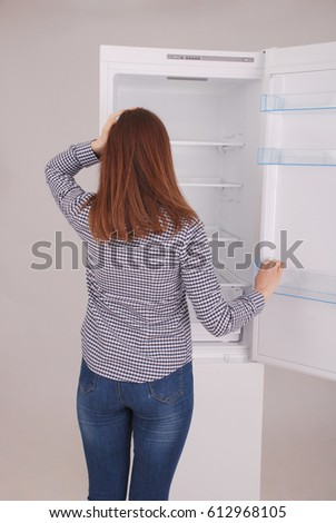 Whats for dinner? Young girl standing near open empty fridge.