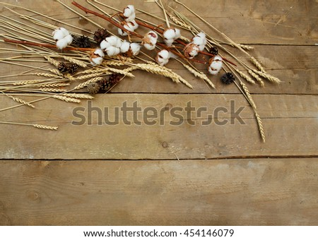 Wheat and cotton lying on a wooden background