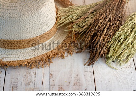 wheat and woman hat on white wooden table top - stock photo