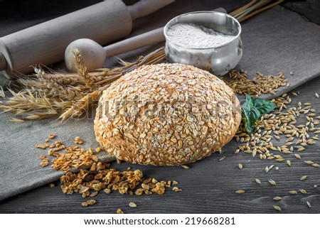 Wheat bran bread on wooden table with wheat and flour on background - stock photo