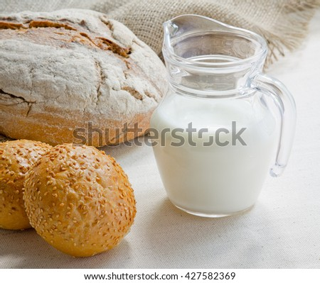 Wheat bread, a jug of milk and bread with sesame seeds