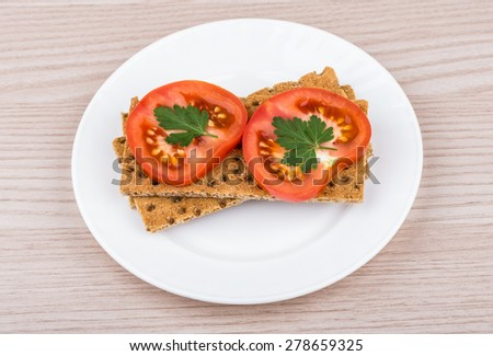 Wheat crisp bread with slice of tomatoes in white glass plate on table - stock photo