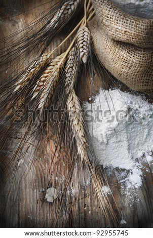 Wheat ears and flour sack on grunge wooden board - stock photo