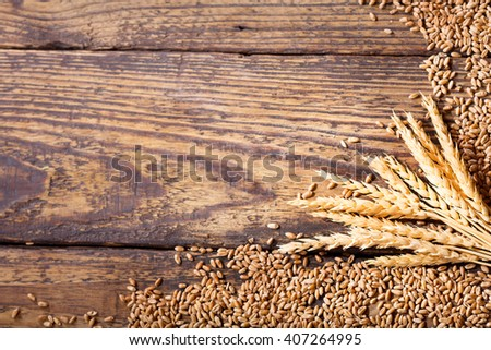 wheat ears and grains on a wooden table - stock photo