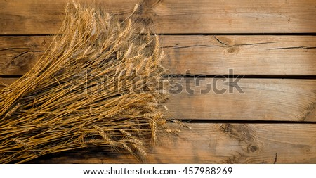 Wheat ears on old wooden background - stock photo
