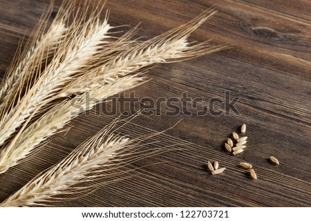 Wheat ears on wooden table - stock photo