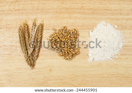 Wheat ears, wheat grains and flower on a wooden board - stock photo