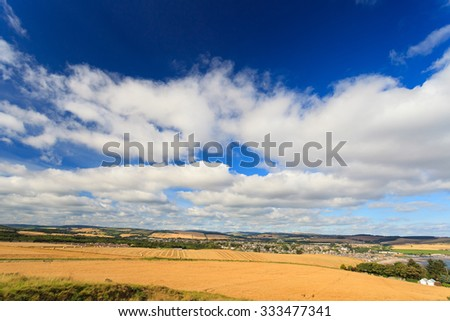 Wheat field and blue sky with clouds at shore line close to North sea, Aberdeen, Scotland, UK - stock photo