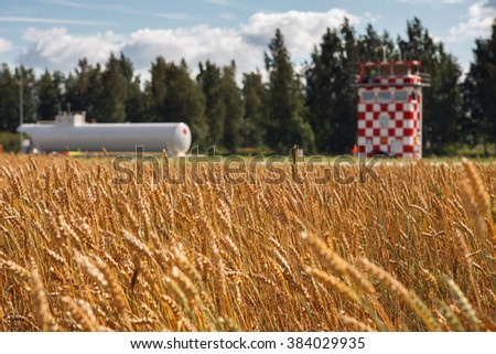 Wheat field, on a background  airport dispatcher tower and fueling station - stock photo