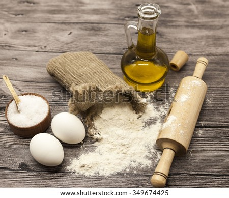 Wheat flour in a canvas bag, the olive oil in a glass carafe, a large salt shaker wood, raw eggs, a wooden rolling pin: set for making homemade bread dough on a beautiful dark wooden background. - stock photo