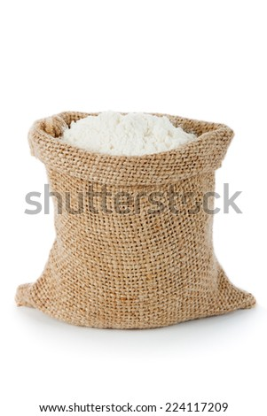Wheat flour in small burlap sack - stock photo