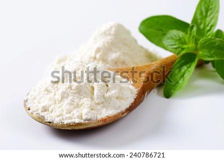 Wheat flour on wooden spoon  - stock photo