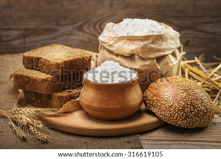 Wheat flour, sliced bread, bun with sesame seeds, wheat ears and straw on an old wooden background - stock photo