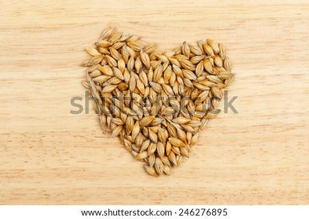 Wheat grains in the shape of a heart on a wooden board - stock photo